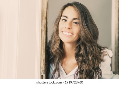 Joyful beautiful young Hispanic woman opening door, standing in doorway, looking at camera and smiling. Closeup shot. Real estate concept