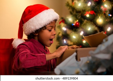 Joyful black boy opens present. Happy child opening Christmas present. Anticipation was worth it. One of many holiday miracles.