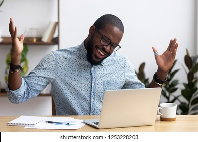 Joyful black businessman sitting at desk looking at computer screen talking with friend make informal video call. African worker received great news read email feels happy getting reward or promotion