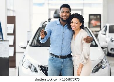 Joyful Black Couple Holding New Car Key Smiling At Camera Posing Standing Near Luxury Auto In Dealership Store