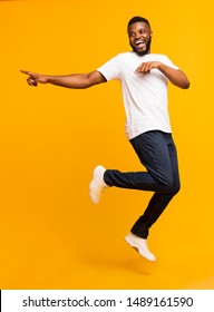 Joyful black millennial guy jumping on air and pointing aside, free space