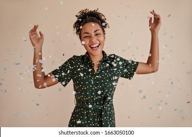 Joyeuse jeune femme noire dansant sous des confettis. Tournage en studio d'une fille afro-américaine étonnante en train de rire isolée sur fond beige.