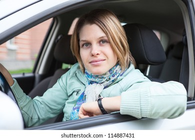 Joyful blond hair woman sitting in land vehicle and looking at camera