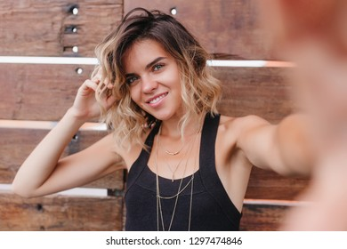 Joyful blue-eyed girl taking picture of herself on wooden background. Spectacular fair-haired european woman making selfie with sincere smile.