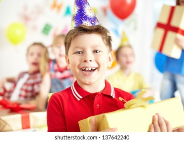 Joyful boy with giftbox looking at camera at birthday party