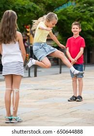 joyful boy and girls in elementary school age jumping over chinese jumping rope at playground . Selective focus on boy