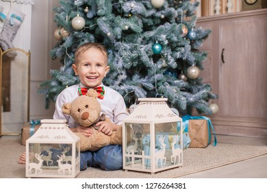 Joyful boy with his favorite toy is sitting under the Christmas tree