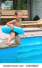 Joyful boy are jumping to the swimming pool