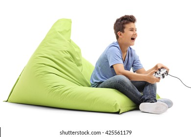 Joyful boy playing video games and laughing seated on a green beanbag isolated on white background