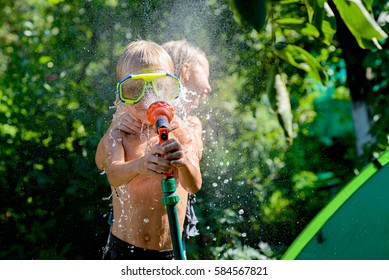 Joyful boy playing with water. The boy in hands holds a garden hose. Focus on boy
