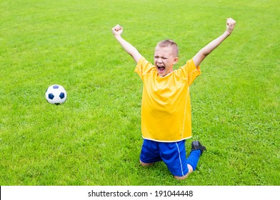 Joyful boy soccer player after goal scored. Natural grass.