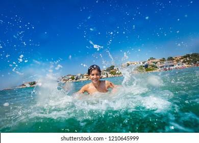 Joyful boy splashing water swimming in the sea
