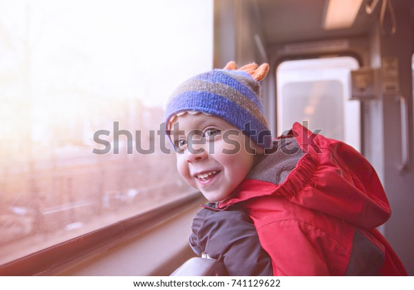 Joyful boy in the subway. child smiling looking out the window of a train. The boy excited by a trip in the subway