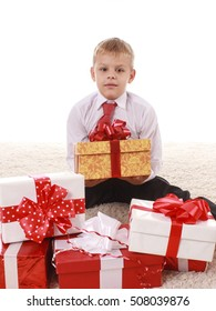 joyful boy teenager thrilled with boxes of gifts in a white shirt and red tie