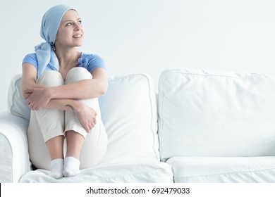 Joyful breast cancer survivor holding her knees while relaxing on a couch