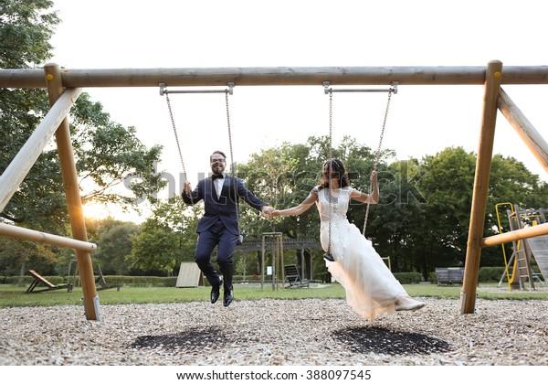 Joyful bridal couple having fun in the swing