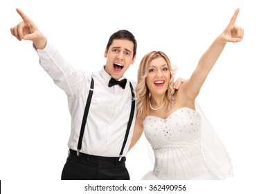 Joyful bride and groom singing together and pointing up with their hands isolated on white background