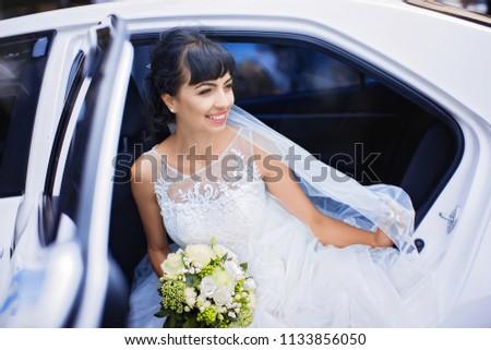 cbd4bb0829d Joyful bride in white wedding dress and veil holds bouquet of roses