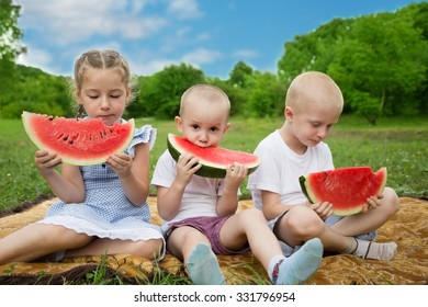 Joyful brothers and sister eating watermelon in the park.