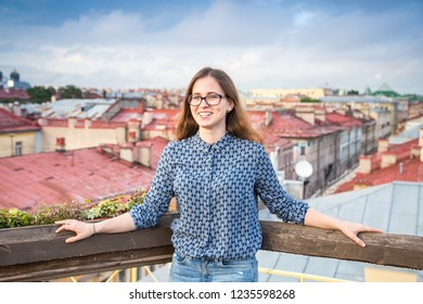 joyful brown-haired young girl wearing blue jeans, blouse and glasses stands on the roof of the building