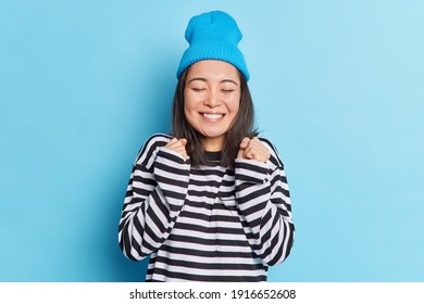 Joyful brunette beautiful Asian woman clenches fists celebrates something makes yes gesture smiles broadly wears hat and striped sweater isolated over blue background. Yeah I finally gained it