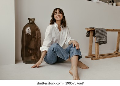 Joyful brunette curly woman in trendy pants and white shirt smiles and looks into camera. Pretty lady in jeans sits on floor in bathroom.
