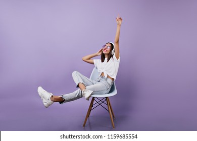 Joyful brunette girl listening music in studio. Relaxed female model in jeans posing on purple background with headphones.