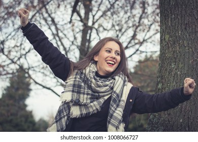 Joyful brunette girl smiling with arms up in the park on cloudy autumn season day. Celebration concept. Pretty young woman happy as if having won the lottery