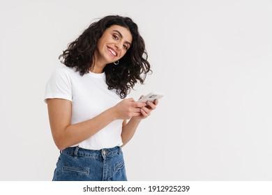 Joyful brunette girl smiling and using mobile phone isolated over white background