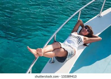 Joyful brunette woman laying on shipboard of yacht. Copyspace