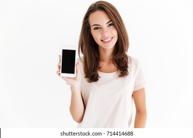 Joyful brunette woman showing blank smartphone screen and looking at the camera over white background