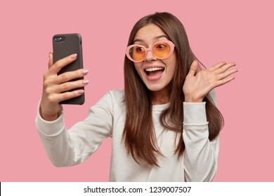 Joyful brunette woman wears sunglasses, waves at camera of smart phone, makes video call, connected to wireless internet, dressed in white jumper, isolated over pink background. Hello, friend