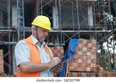 Joyful builder in helmet writing document on a building site