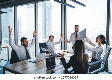 Joyful business team in formal wear sitting around table with raised hands and open laptops tossing up papers celebrating success in office