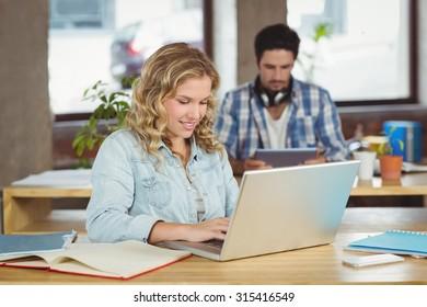 Joyful business woman working on laptop in creative office