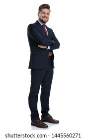 Joyful businessman standing with his arms folded and smiling while wearing a blue suit and red tie, standing on white studio background