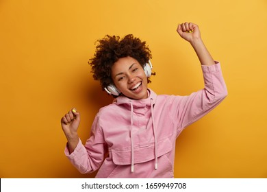 Joyful carefree woman dances to music, listens favourite audio track, raises hands with clenched fists, smiles broadly, wears rosy sweatshirt, isolated over yellow wall. People, leisure, entertainment