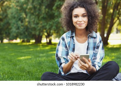Joyful casual african-american student girl with laptop outdoors. Smiling woman sitting on grass with computer, surfing the net or preparing for exams. Technology, education and remote working concept