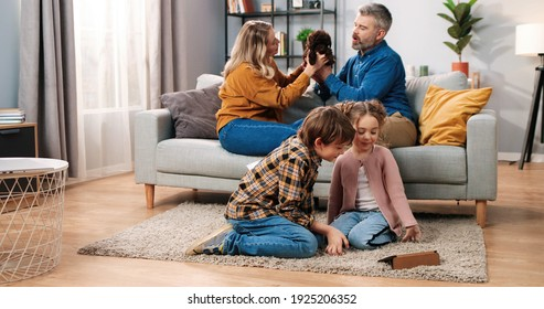 Joyful Caucasian family spending time at home. Happy kids little boy and girl sitting on floor watching videos or cartoons on tablet while parents playing with pet puppy dog on sofa, leisure concept