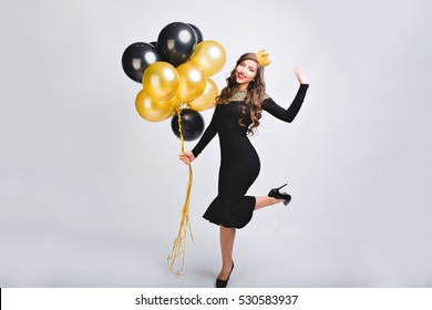 Joyful charming young woman in luxury black dress on heels celebrating new year in studio.  Gold crown on head. Having fun with  yellow and black balloons, disco party, carnival, happy emotions