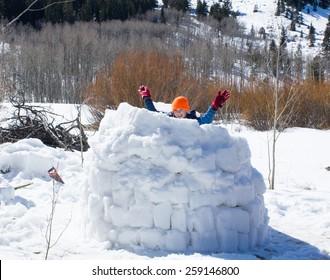 Joyful child almost finished Eskimo dwelling - igloo