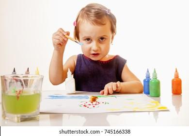 Joyful child girl painting. (Creativity, education, child development in art, happy childhood, abilities concept)