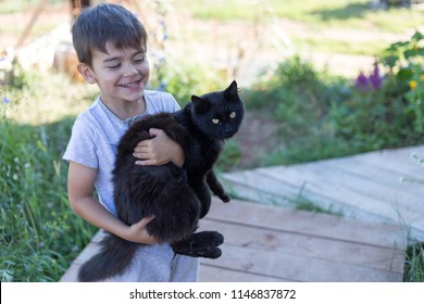 A joyful child holds a cat in his arms. the boy caught a black cat