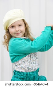 The joyful child on white in a yellow beret keeps hands for a fencing