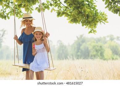 Joyful child swinging near parent
