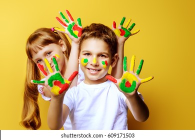Joyful children with paints on their faces and palms. Drawing. Creativity and education concept. Yellow background.