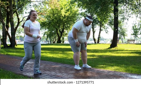Joyful chubby girl outrunning obese man tired after jogging, exhausting workouts