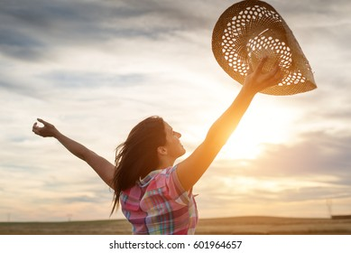 Joyful countryside young woman raising arms towards the sunset in a harvested field. Rural lifestyle freedom and success concept.