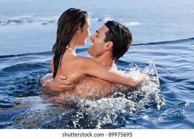 Joyful couple cuddling each other in a swimming pool