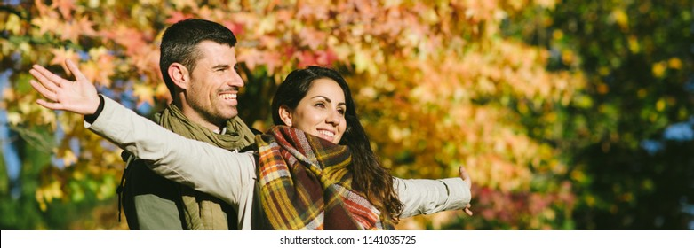 Joyful couple having fun together in autumn banner. Blissful man and woman enjouing leisure together.